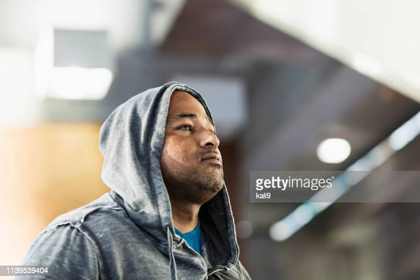serious mature hispanic man in hooded shirt - one mature man only stock pictures, royalty-free photos & images