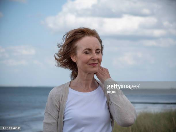 serious mature woman at beach. - medium shot stock pictures, royalty-free photos & images