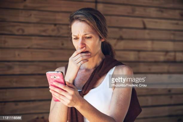 serious mature woman looking at smart phone - ショック ストックフォトと画像