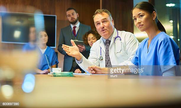 serious medical meeting - nhs staff stock pictures, royalty-free photos & images