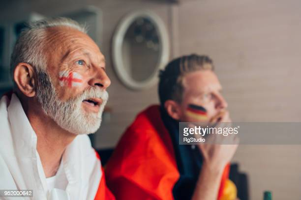 serious men supporting uk and german soccer teams - sports jersey stock pictures, royalty-free photos & images
