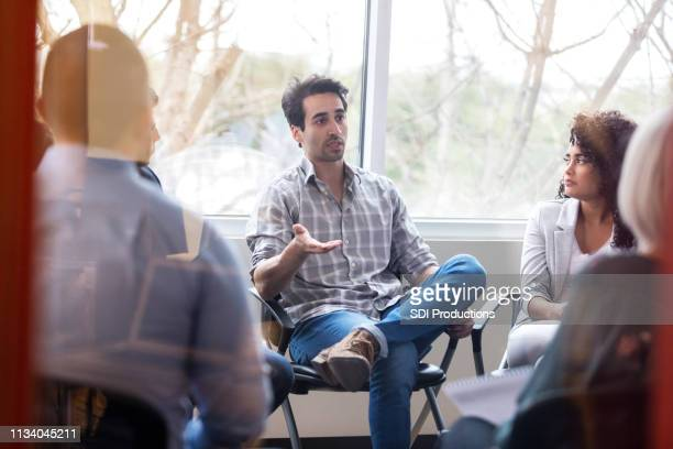 serious mid adult man talks during support group meeting - mid adult men stock pictures, royalty-free photos & images