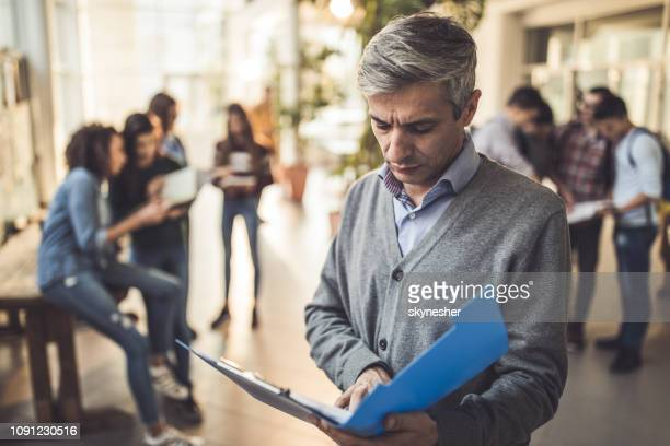 serious mid adult professor reading documents in a hallway. - school principal stock pictures, royalty-free photos & images