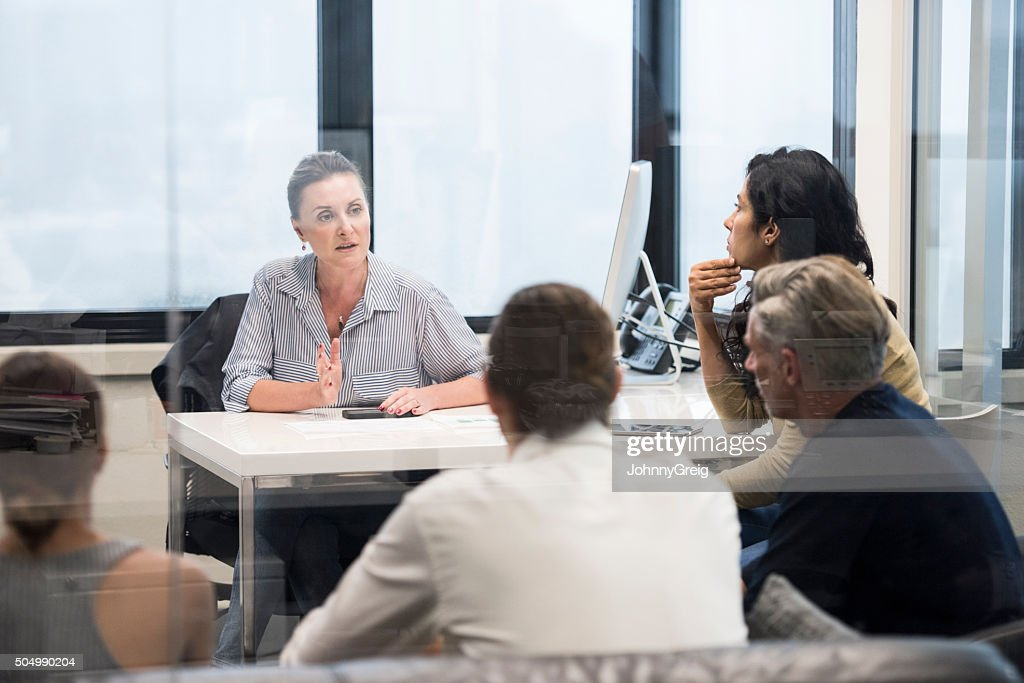 Serious mid adult woman in business meeting explainign to colleagues : Stock Photo