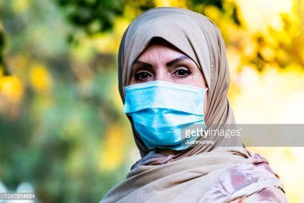 保護フェイスマスクを着用してカメラを見ている深刻な中東のイスラム教徒の女性 - 僧衣 ストックフォトと画像