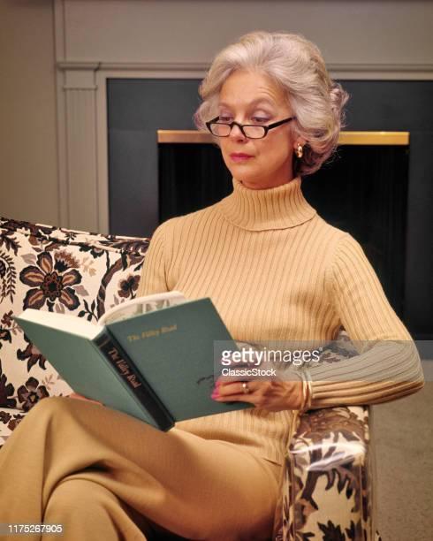 Serious MiddleAged Gray Hair Woman Sitting On Living Room Sofa Wearing Turtleneck Reading Eyeglasses Enjoying A Book