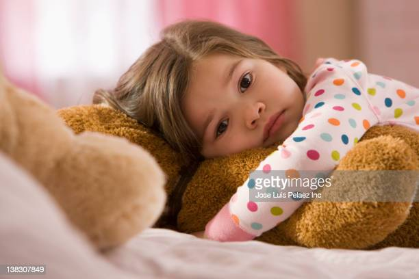 serious mixed race girl hugging teddy bear - vulnerability stock pictures, royalty-free photos & images