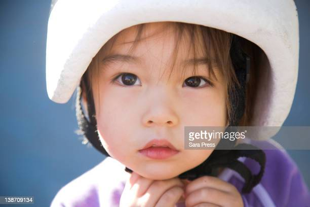 serious mixed race girl in helmet - putting stock pictures, royalty-free photos & images