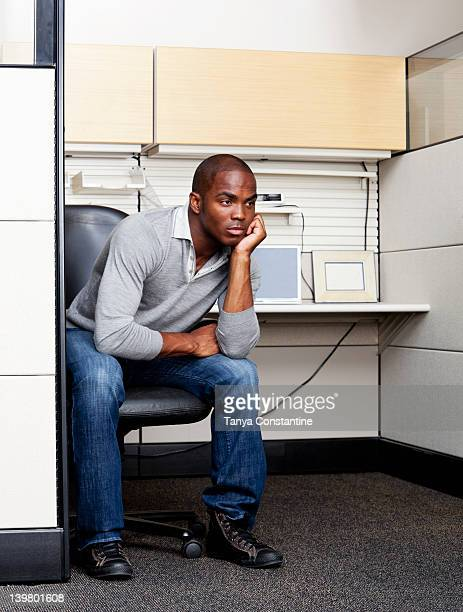 Serious mixed race man sitting in office cubicle
