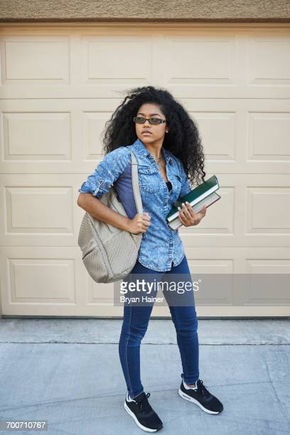 serious mixed race teenage girl standing in driveway holding books - las vegas girls stock photos and pictures