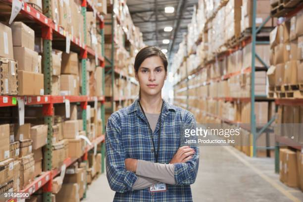 Serious mixed race woman with arms crossed in warehouse