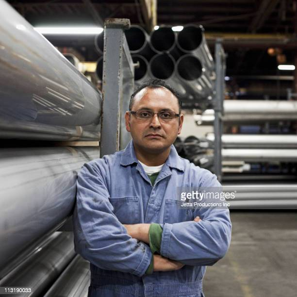 Serious mixed race worker standing near metal pipes in factory