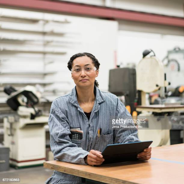 Serious Mixed Race worker using digital tablet at table in factory