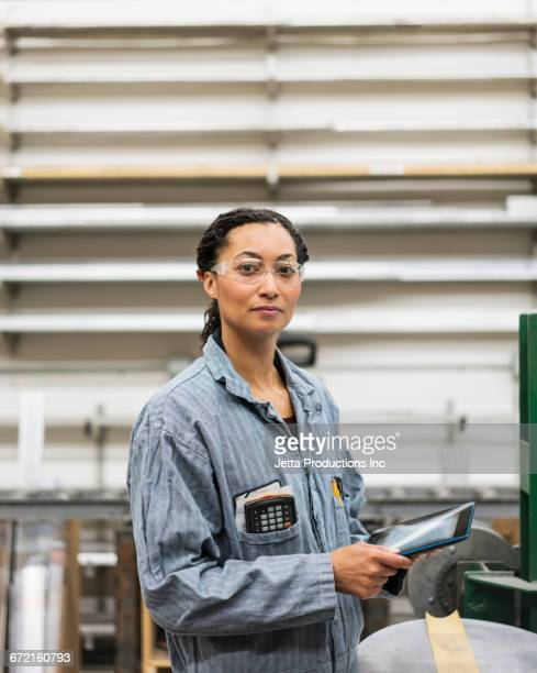 Serious Mixed Race worker using digital tablet in factory