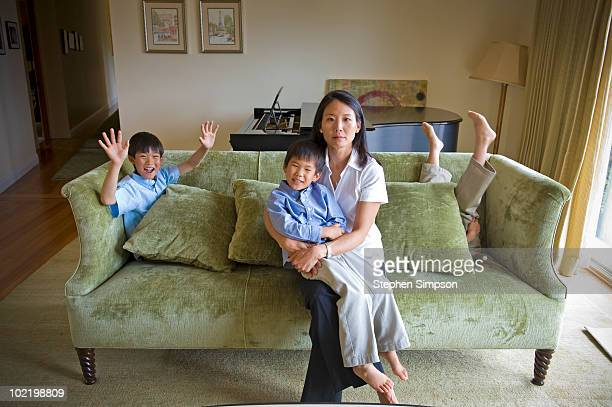 serious Mom and three sons on their couch