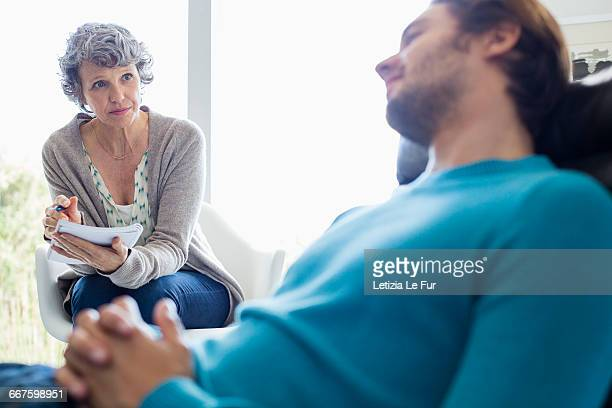 Serious mother and son sitting together in living room