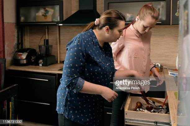 serious natural middle-aged mother with pony tail wearing plus size clothing finding kitchen utensil in box while helping adult daughter to cook at kitchen - domestic kitchen stock pictures, royalty-free photos & images