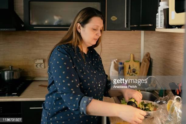 serious natural plus-size woman with double chin standing at kitchen counter and cooking fresh salad, she being on diet - fat nutrient stock pictures, royalty-free photos & images