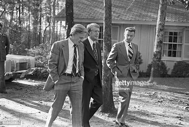 Serious new Carter appointees Charles Schultz and Zbigniew Brzezinski walk along with their boss to his home after Presidentelect made announcement...
