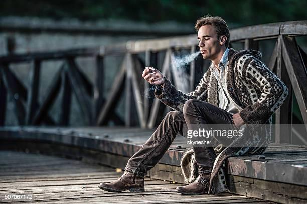 Grave ancienne homme assis sur le pont et les fumeurs de cigare.