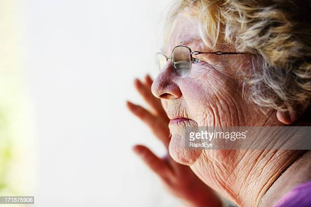 serious old lady looks through window - liver spot stock photos and pictures