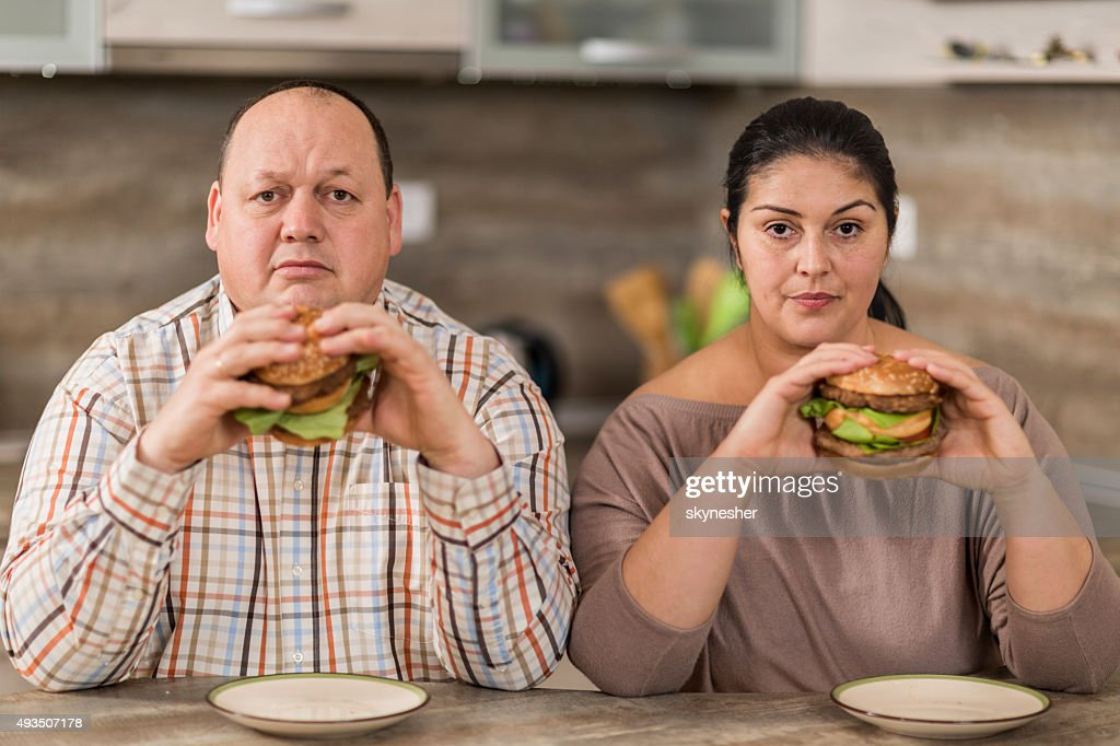Serious overweight couple eating burgers in the kitchen. : Stock Photo