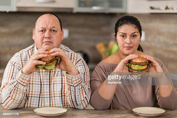 Serious overweight couple eating burgers in the kitchen.