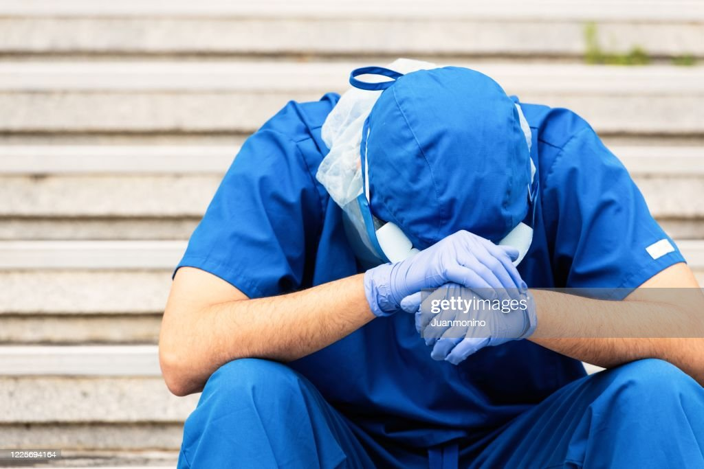 Serious, overworked, very sad male health care worker : Stock Photo