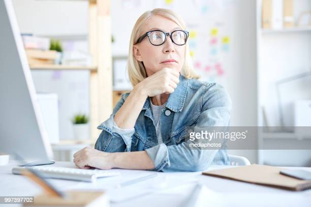 serious pensive attractive female graphic designer in glasses wearing denim jacket thinking of project and looking away while working in office - creative director stock pictures, royalty-free photos & images