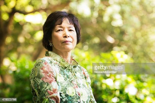 Serious pensive confident Japanese senior woman portrait in Tokyo park