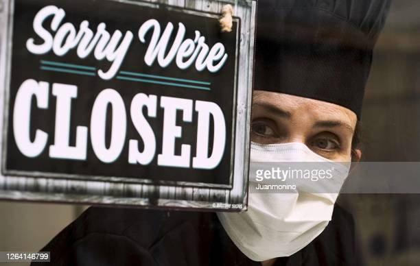 serious pensive female chef looking through her restaurant window near a closed sign - government shutdown stock pictures, royalty-free photos & images