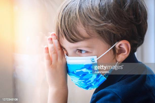 serious pensive little child boy wearing a protective face mask posing looking through a window - uncertainty stock pictures, royalty-free photos & images