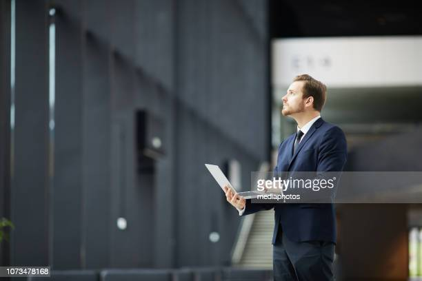 Serious pensive young bearded businessman in formal suit standing in lobby with tall ceiling and looking up while holding laptop and thinking about project