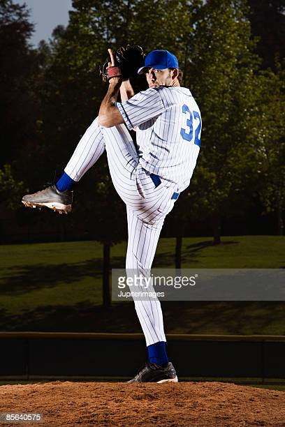 serious pitcher standing on pitcher's mound - baseball pitcher stock pictures, royalty-free photos & images