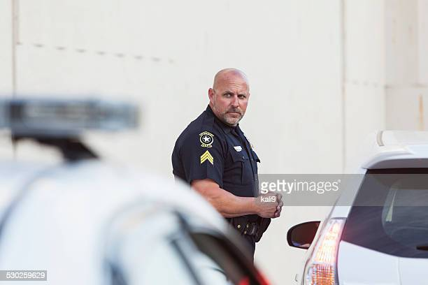 Serious police officer standing next to car
