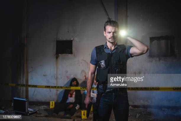 serious police officer with flashlight shining at camera - crime scene stock pictures, royalty-free photos & images