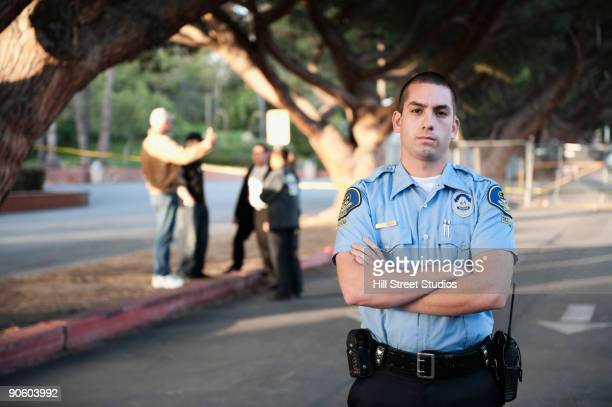 serious policeman standing with arms crossed - justiça criminal - fotografias e filmes do acervo