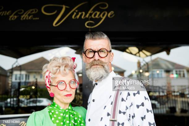serious portrait of a quirky vintage couple outside vintage shop - freaky couples stock photos and pictures