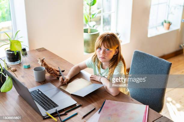 serious redhead girl doing homework in front of laptop at home - bangs hair stock pictures, royalty-free photos & images