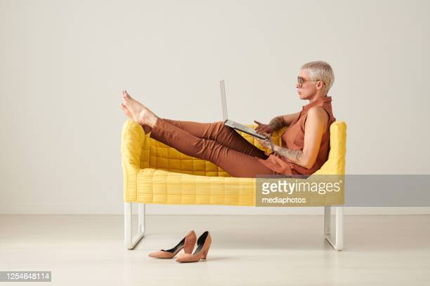 serious relaxed business lady with short blond hair sitting on yellow sofa and surfing websites on laptop - fashionable stock pictures, royalty-free photos & images