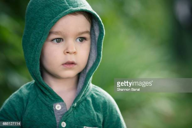 serious scared boy looks away from camera - hood clothing stock photos and pictures