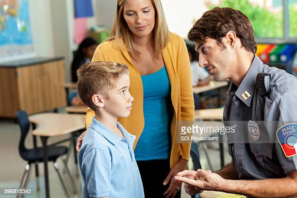 serious school security officer talks with male student - charter_school stock pictures, royalty-free photos & images