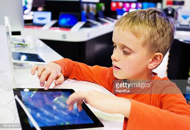 serious schoolboy sitting in computer store trying out tablet-style pc - digital native stock pictures, royalty-free photos & images