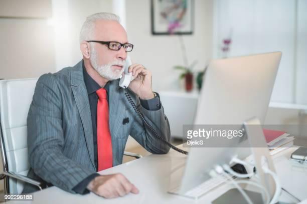 ernstige senior zakenman beantwoorden van een telefoongesprek voeren in office. - 65 69 jaar stockfoto's en -beelden