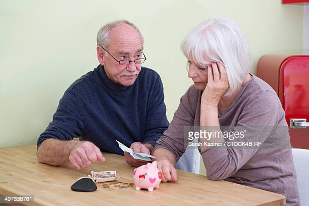 Serious senior couple counting money