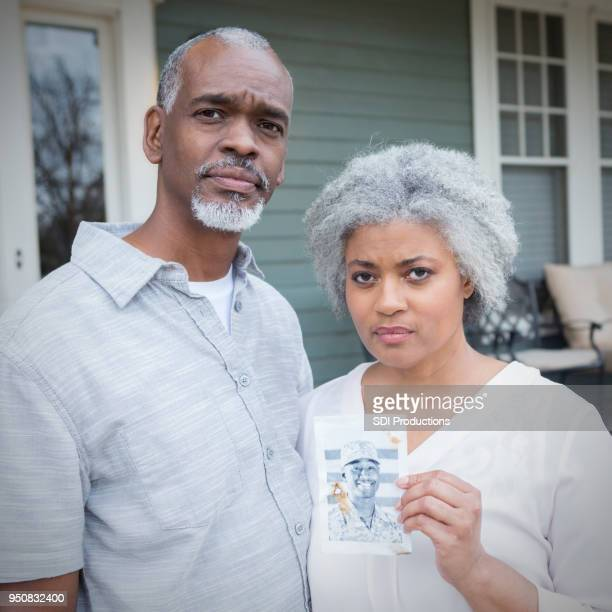 serious senior couple hold photo of military son - beautiful wife pics stock pictures, royalty-free photos & images