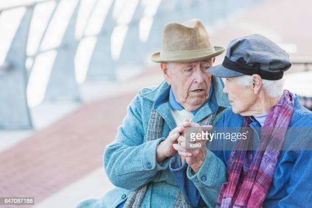 Couple de personnes âgées sérieux assis tenant à l'extérieur des mains