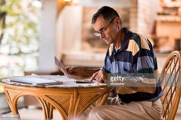 serious senior man calculating home finances on the terrace. - filing documents stock pictures, royalty-free photos & images
