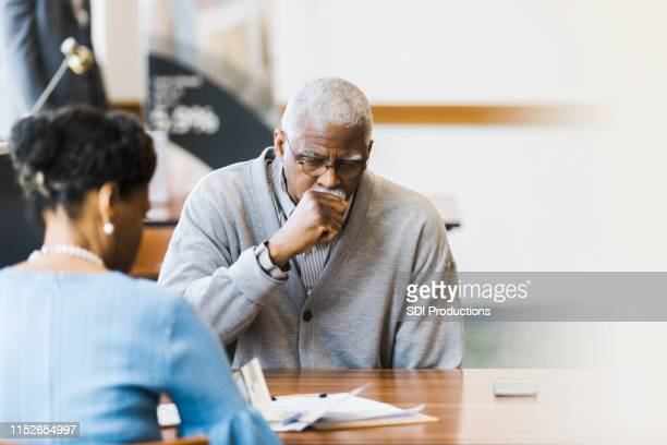 serious senior man meeting with loan officer - cough stock pictures, royalty-free photos & images