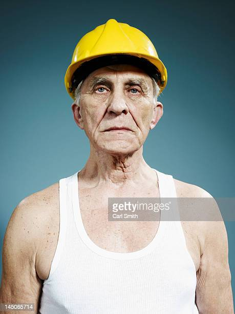 A serious senior man wearing a hardhat and tank top
